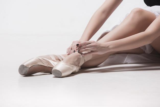 Ballerina-tänzerin, die sich mit gekreuzten beinen auf den weißen studioboden setzt