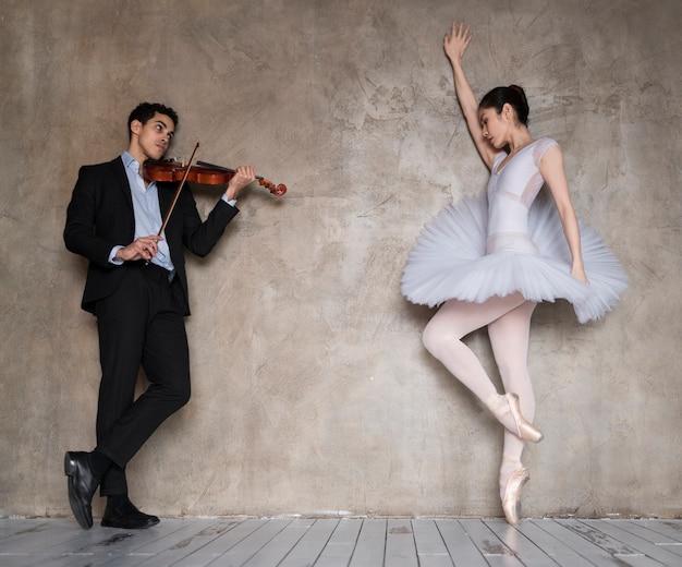 Ballerina tanzt zu musik, die von einem männlichen musiker gespielt wird