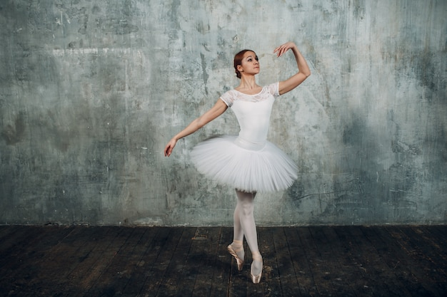 Ballerina weiblich. junge schöne frau balletttänzerin, gekleidet in professionelles outfit, spitzenschuhe und weißes tutu.
