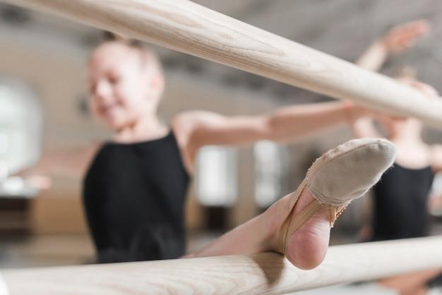 Ballerinamädchen, das ihr bein bei barre ausdehnt