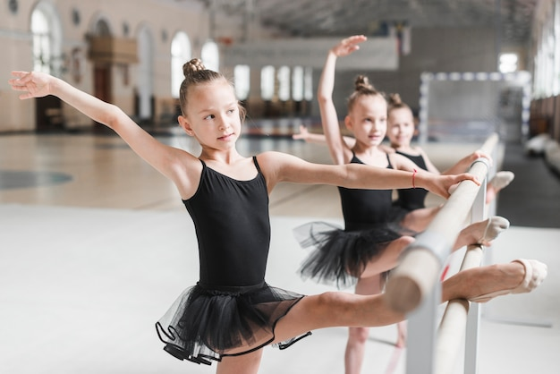 Ballerinamädchen im schwarzen ballettröckchen, das ihre beine auf stange ausdehnt