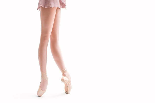Ballerinas füße in spitzenschuhen, die lokal auf einem weißen hintergrund stehen
