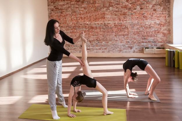 Ballerinas probe. jugendsportleben. rhythmische gymnastik für mädchen im tanzunterricht mit trainerin. gym hintergrund, gesunder lebensstil, trainingskonzept