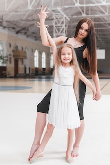 Ballerinastrainer mit ihrem studenten, der in der tanzklasse aufwirft