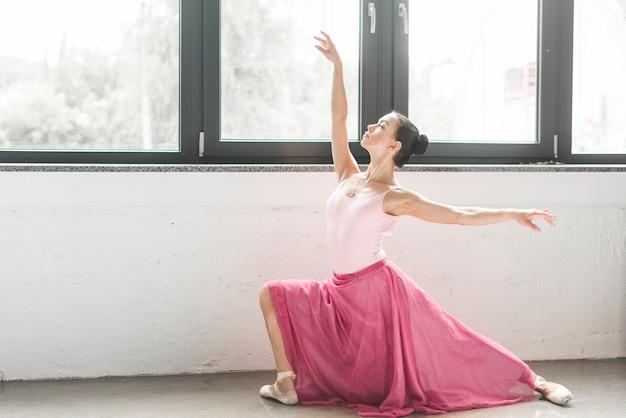 Ballerinatänzer, der nahe dem fenster tanzt