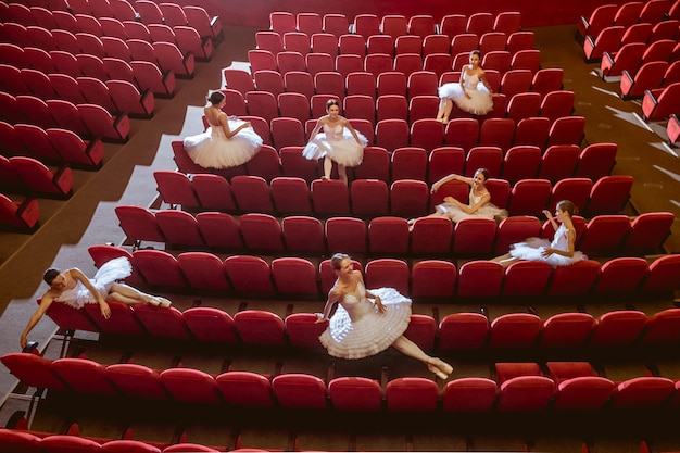 Ballerinen, die im leeren auditoriumstheater sitzen