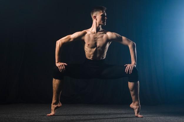 Ballerino in strumpfhose posiert mit gespreizten beinen