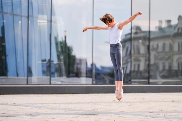 Ballettjunge teenager tanzen in einem sprung vor dem hintergrund von stadt- und himmelsreflexionen in einer glaswand