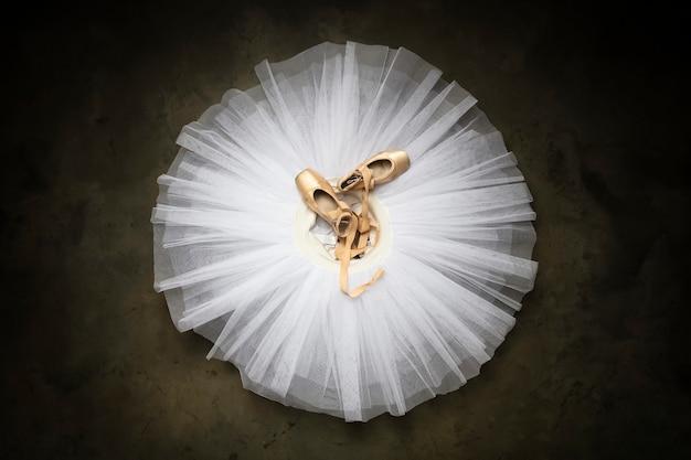 Ballettschuhe mit bändern auf einem weißen tutu in einem tanzstudio