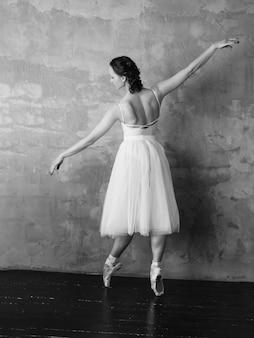 Balletttänzer-ballerina im schönen weißen kleid-ballettröckchenrock, der im dachbodenstudio aufwirft