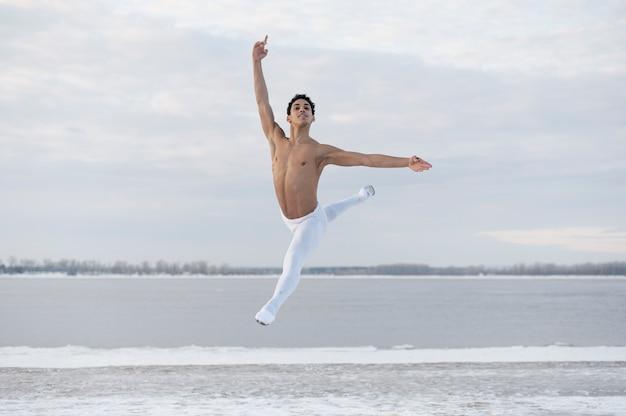 Balletttänzer, der elegante haltung durchführt