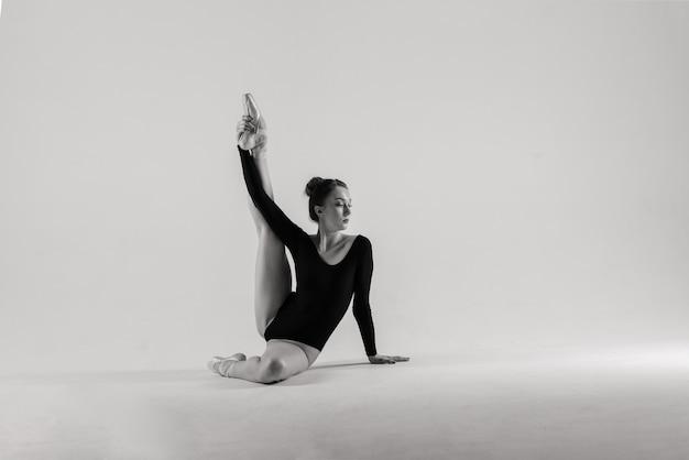 Balletttänzer des modernen stils, der auf einem studiohintergrund aufwirft