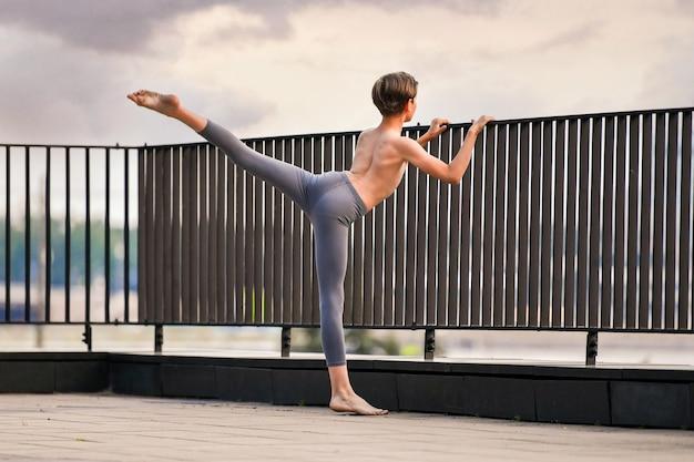 Balletttänzer jugendlicher junge, der auf sonnenunterganghimmelhintergrund auf dem dach trainiert