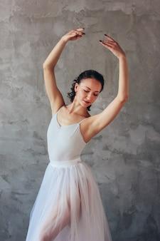 Balletttänzerballerina im schönen hellblauen kleidetuerrock, der im dachbodenstudio aufwirft