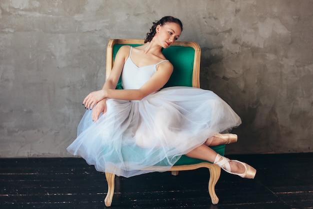Balletttänzerballerina im schönen hellblauen kleidetuttrock, der das sitzen auf vinage stuhl im dachbodenstudio aufwirft