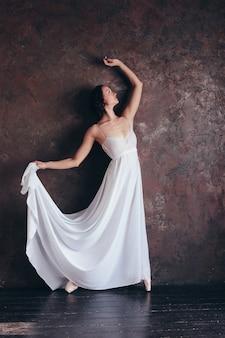 Balletttänzerballerina im weißen kleid des schönen dünnen fliegens wirft im dunklen dachbodenstudio auf
