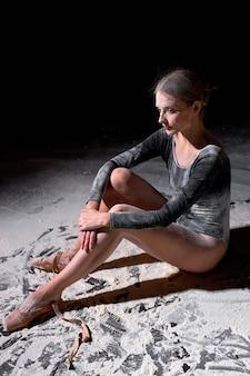 Balletttänzerin ist nach dem training müde. junge kaukasische balletttänzerin, die mit mehl auf dem boden sitzt und während des ballettunterrichts spitzenschuhe auszieht. erschöpfung, müdigkeit, schwierigkeiten