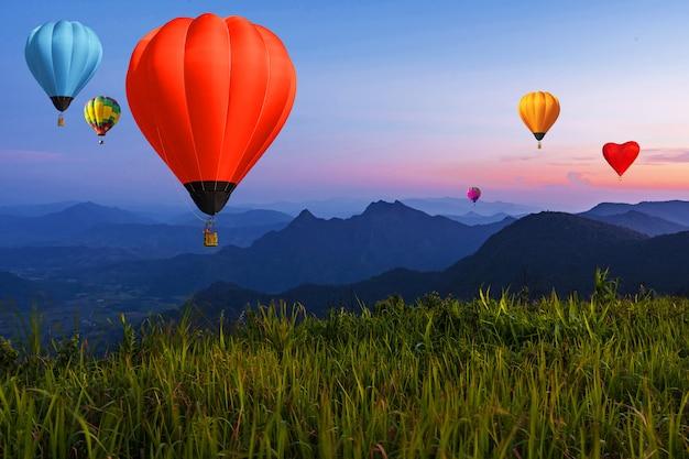 Ballon auf dämmerungshimmel über hochgebirgssichtspunkt bei sonnenuntergang