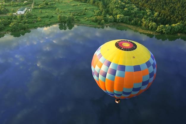 Ballon über dem see, blick von der drohne. gelber und blauer ballon auf einem hintergrund der morgendämmerung.
