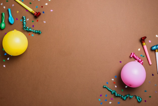 Ballons; konfetti; luftschlangen und partyhornbläser an der ecke der kulisse