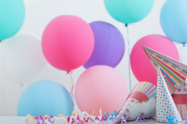 Ballons und geburtstagshüte auf festlichem hintergrund