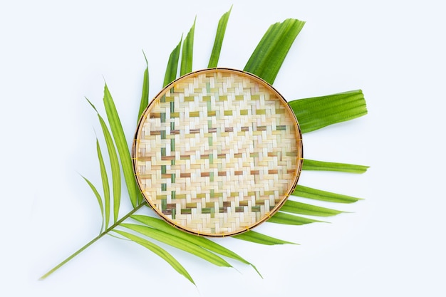 Bambus-dreschkorb aus holz auf tropischen palmblättern