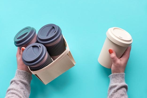 Bambus-kaffeetassen, tassen oder reisebecher in einer schachtel aufbewahren. box ist in weiblicher hand auf blauem minzhintergrund. kreative flache lage, draufsichtbild.