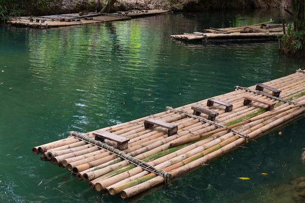 Bambusfloß eine art, auf dem wasser zu reisen. der mensch seit der antike verwendet. wasserfall in tha