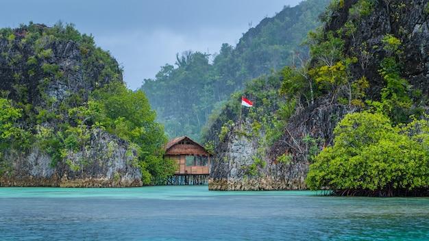Bambushütte zwischen einigen felsen unter regen in der bucht, pianemo-inseln, raja ampat, west-papua, indonesien