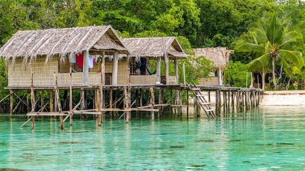 Bambushütten auf hölzernen beständen einer gastfamilie, gam island, west papuan, raja ampat, indonesien