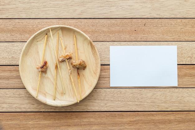 Bambusstock der draufsicht leerer gegrillter schweinefleisch- und papieranmerkung über hölzernen teller