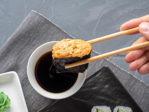 Bambusstöcke halten ein scharfes gunkan. im hintergrund steht eine schüssel sojasauce. nahaufnahme. traditionelle japanische küche