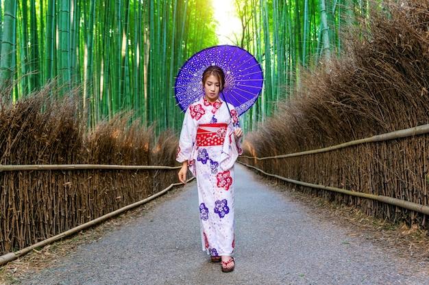 Bambuswald. asiatische frau, die traditionellen japanischen kimono am bambuswald in kyoto, japan trägt.