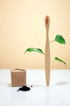 Bambuszahnbürste aus holz mit blättern und schwarzer holzkohle-zahnpasta als umweltfreundliches kreativkonzept