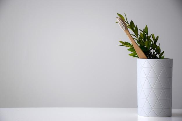 Bambuszahnbürste im weißen halter mit grünem blatt