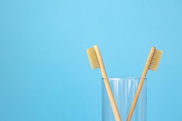 Bambuszahnbürsten auf blauem hintergrund in einem glas umweltfreundliche körperpflegeprodukte für menschen