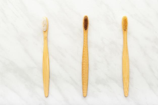 Bambuszahnbürsten auf weißem marmortisch. zahnpflege