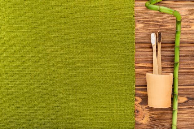 Bambuszahnbürsten, bambuspflanze, zahnputzmittelzahnpulver auf hölzernem hintergrund. flache kopienraum. biologisch abbaubare natürliche bambuszahnbürste. umweltfreundlich, zero waste, zahnpflege plastikfreies konzept.