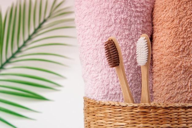 Bambuszahnbürsten mit handtüchern in einem weidenholzkorb