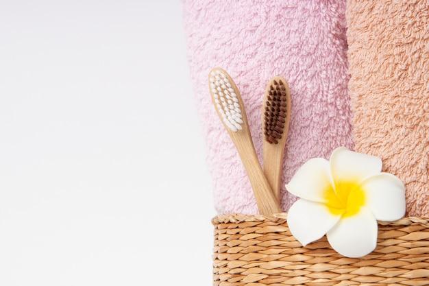 Bambuszahnbürsten mit handtüchern mit copyspace. spa, gesunder lebensstil und ökologiekonzept.