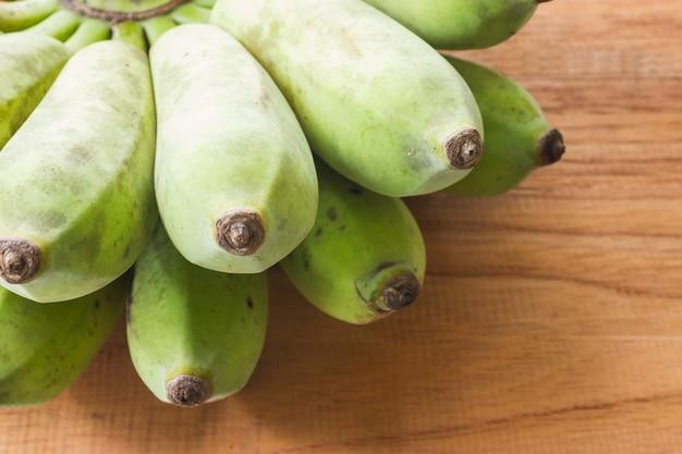 Banane, angebaute banane auf hölzernem hintergrund.