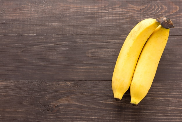 Banane auf dem hölzernen hintergrund. ansicht von oben