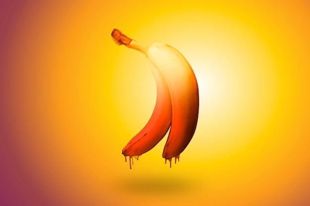 Banane auf einem hell erleuchteten orangefarbenen hintergrund mit einem schokoladentropfen