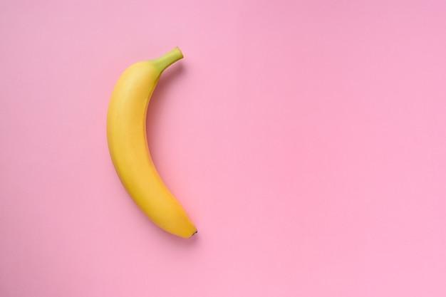 Banane auf rosa oberfläche.