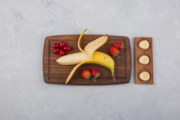 Banane, erdbeere und beeren auf einer holzplatte in der mitte