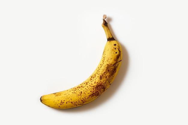 Banane mit dunklen punkten, überreife früchte auf weißem hintergrund. essen mit bedacht konsumieren