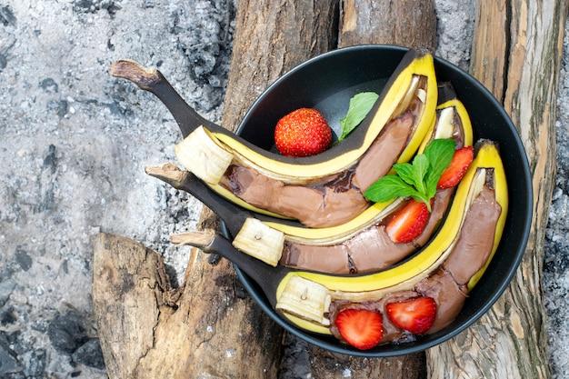 Banane mit schokolade grillen. picknick-dessert-idee. süße bananen in einem teller auf holzkohle. draufsicht.