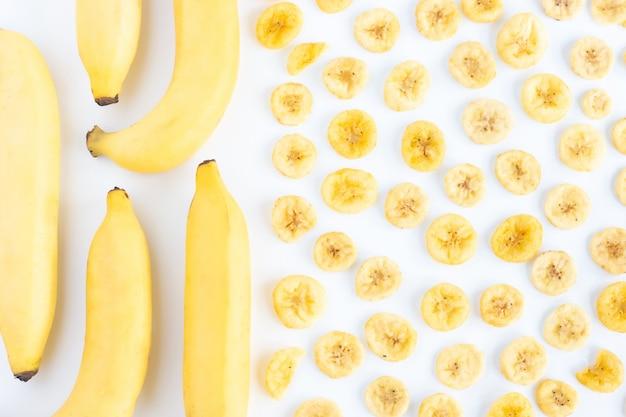 Banane mit stapel der getrockneten banane schneidet den vollen raum, der auf weiß lokalisiert wird