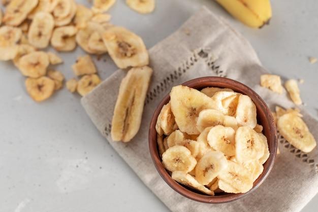 Banane. schüssel voll getrockneter bananenchips. aufnahme mit geringer schärfentiefe und vignettierung.