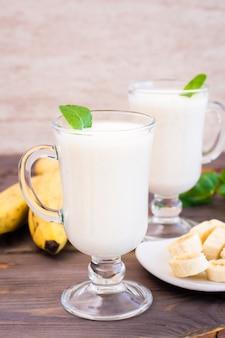 Banane smoothie mit tadellosen blättern in den gläsern auf einer hölzernen tabelle